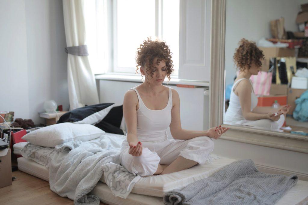 Vrouw in kleermakerszit op onopgemaakt bed
